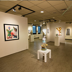 Wide view of paintings and sculpture in the Tom Thomas Art Gallery.