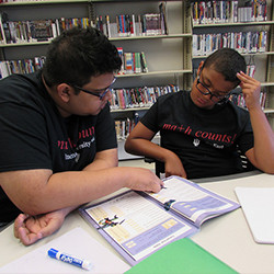 IU East student involved in the Library's Service Learning program tutoring younger math student.