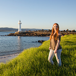 Female student posing in front of lighthouse in Australia.