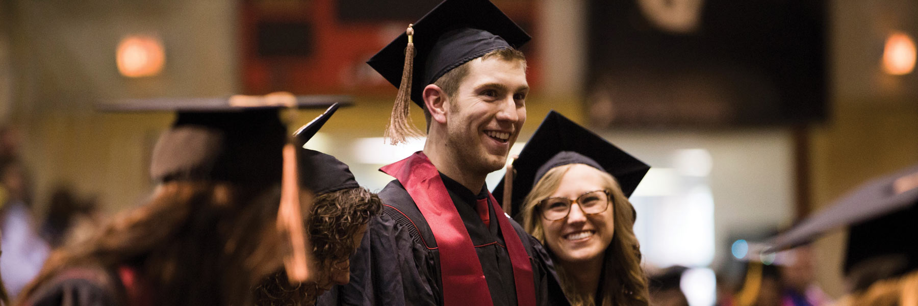 Young man smiling and celebrating his graduation during commencement.