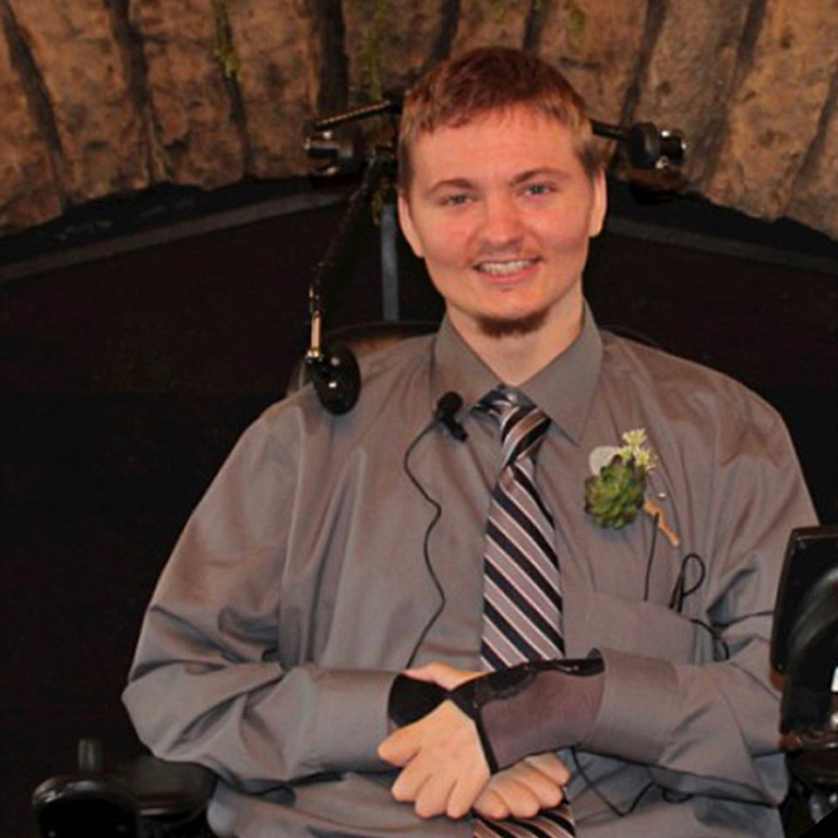 Austin McNew smiling, wearing a tie and boutonniere, and seated in his wheelchair.