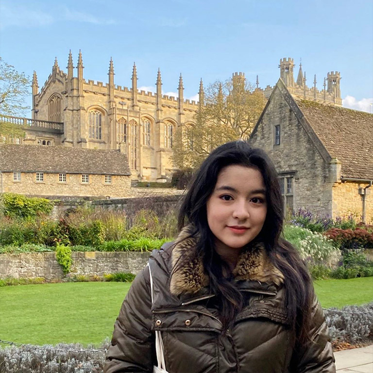 Kiki Pichini smiling while standing in front of beautiful historic buildings.