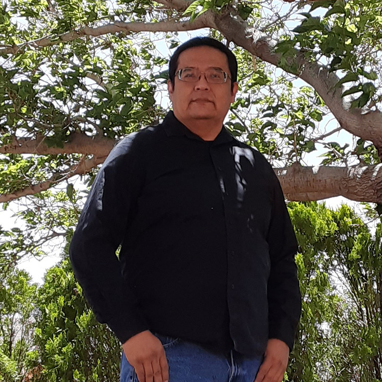 Lawrence Alfred standing in front of a tree in Arizona.