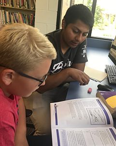 IU East student reads individually with a young student