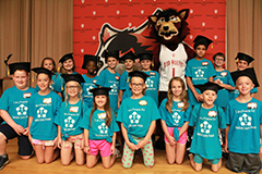 a class of third graders pose with Rufus the Red Wolf