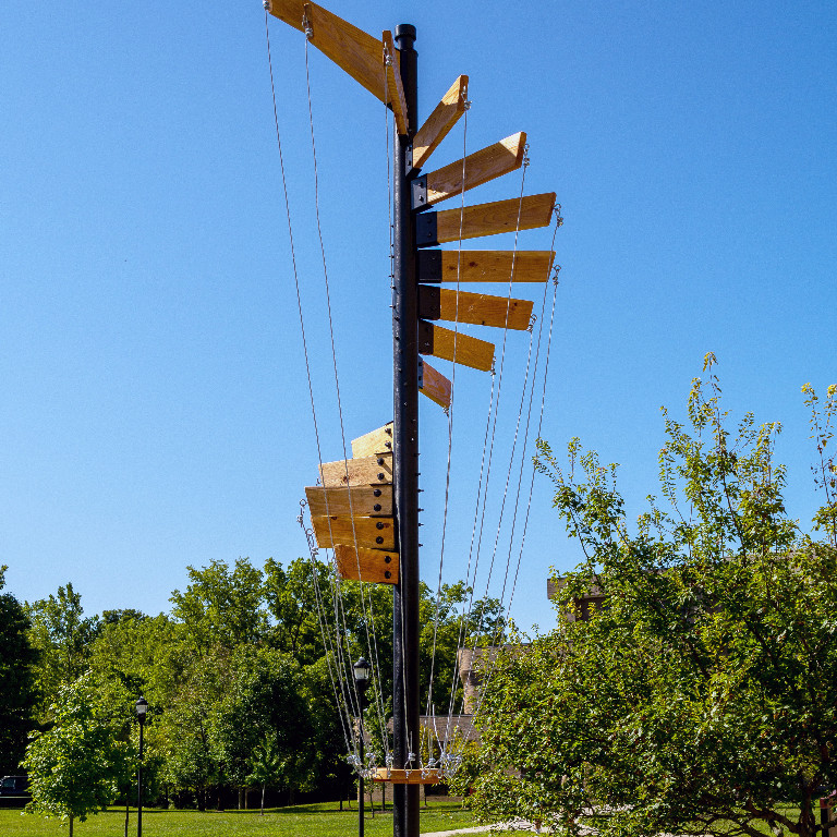 outdoor sculpture features iron and wood sail