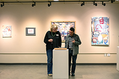 two women view a piece of art in the gallery