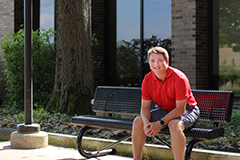 casual portrait of Samuel Roberts sitting outside