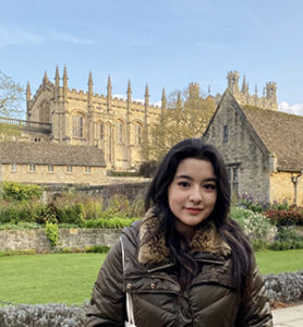 Kiki Pichini stands in front of a scenic church background