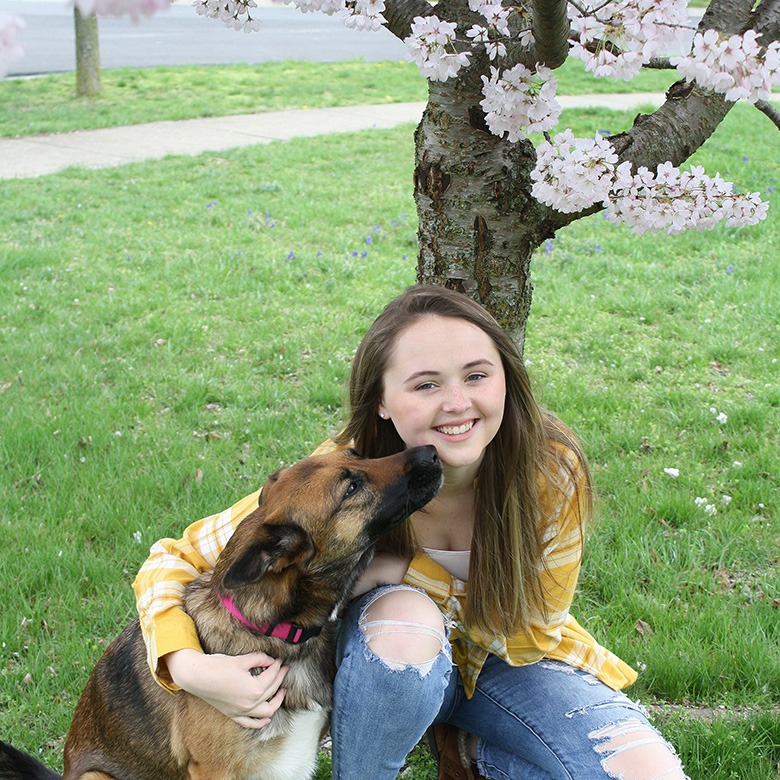 Jillian Splawn sits in front of a flowering tree with a dog