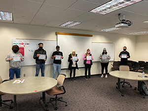 group of students in the classroom holding certificates