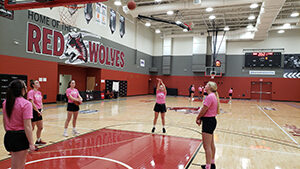 basketball players lined around the free throw lane in pink t-shirts one player shooting the ball