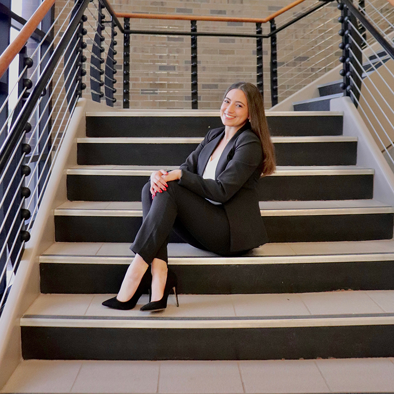 portrait of Andrea Hernández in a black suit sitting in the stairwell of Springwood Hall