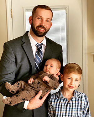 family photo of Ryan Ashlock holding his infant son, Rhys, and standing next to Spencer
