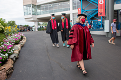 Two graduates Shelby Rogers and Nicole Melichar walk behind Dean Denise Smith at the WSO