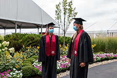 Graduates face each other to talk wearing masks and distanced