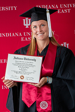 Shelby Rogers stands in front of the red IU East backdrop holding her diploma